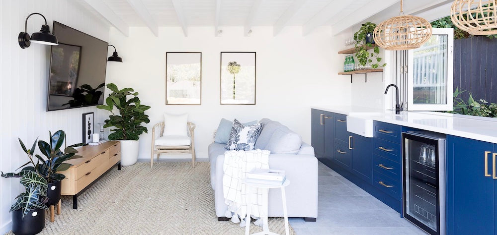 Blue, green and white were the answer when styling this soft grey sofa set against the deep blue cabinetry. Image: Heliconia / Simon Whitbread