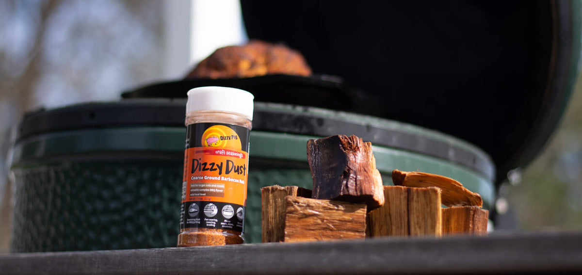 Dizzy Dust Dizzy Pig BBQ Rubs Next to Big Green Egg with Wood Chunks