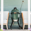 Big Green Egg Medium in nest on deck verandah with green wall behind it.