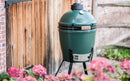 Big Green Egg Medium in nest in brick courtyard garden.