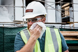 construction worker on a job site wiping face with cleaning wipes