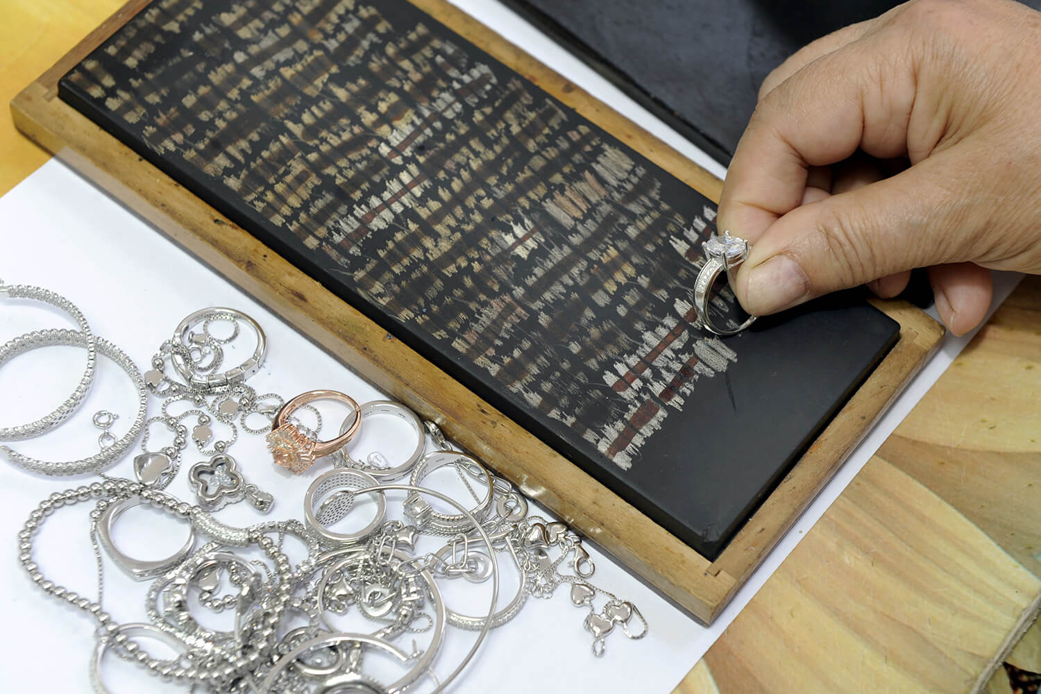 Someone scratches a piece of jewelry against a touchstone in preparation for an acid test.