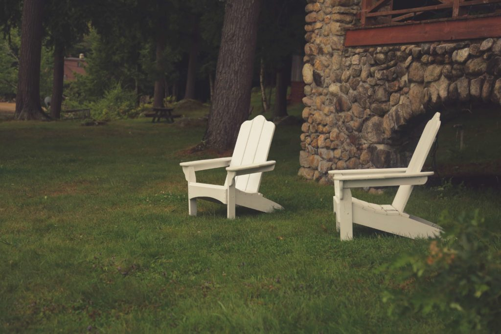 Two Adirondack chairs in a backyard with plush grass
