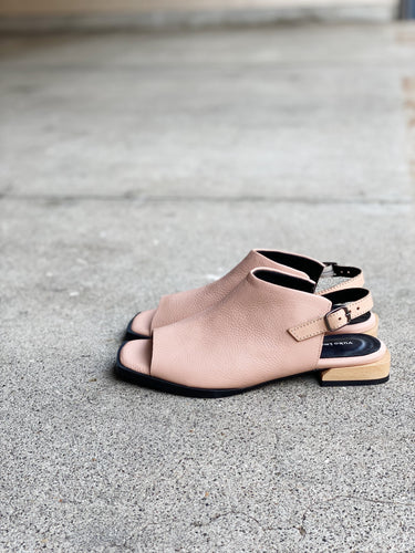 A classic flat sandal in a soft pale pink leather and a wooden sculpted heel by Japanese designer yuko imanishi+