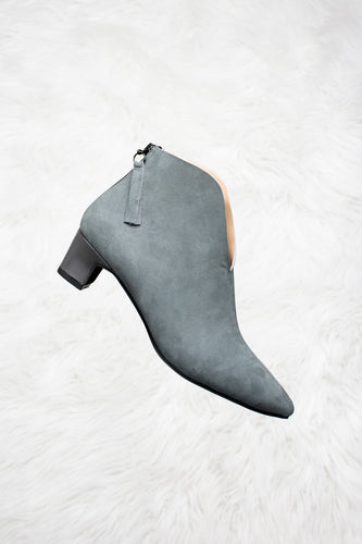 Grey suede boots with a grey leather heels.