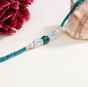 Blue agate and white agate rakhi in teal flat woven thread