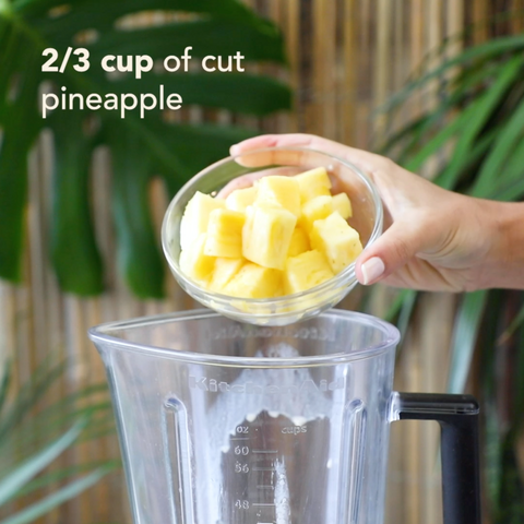Adding 2/3 cup cut pineapple to a blender