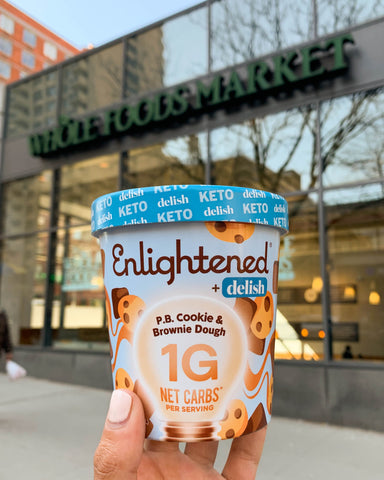 A pint of Enlightened P.B. Cookie & Brownie Dough ice cream in front of a Whole Foods Market store