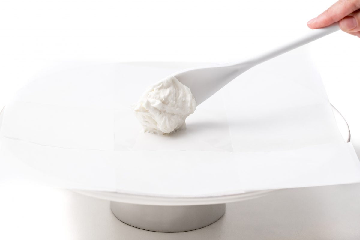 ADD A SMALL AMOUNT OF BUTTER CREAM TO THE PARCHMENT PAPER ON THE CAKE STAND