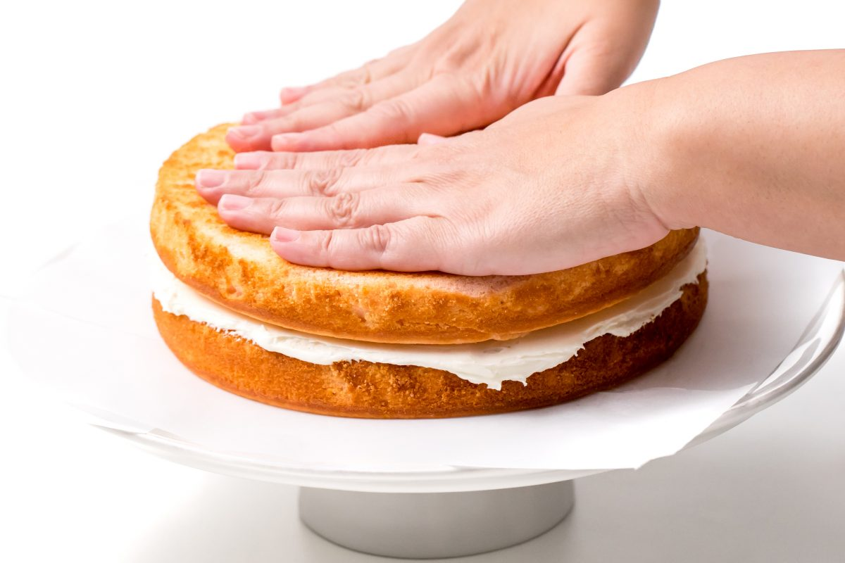 LAY A SECOND LAYER OF CAKE ON TOP AND REPEAT THE ICING.