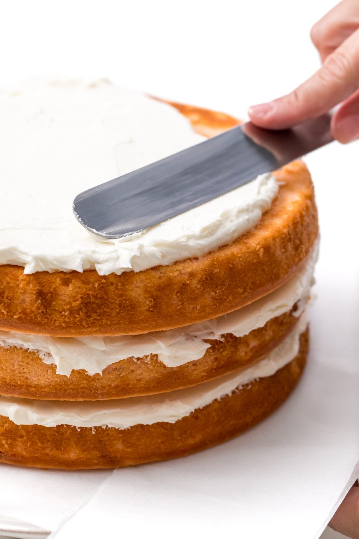 DISTRIBUTE THE ICING EVEN OVER THE LAST LAYER OF CAKE