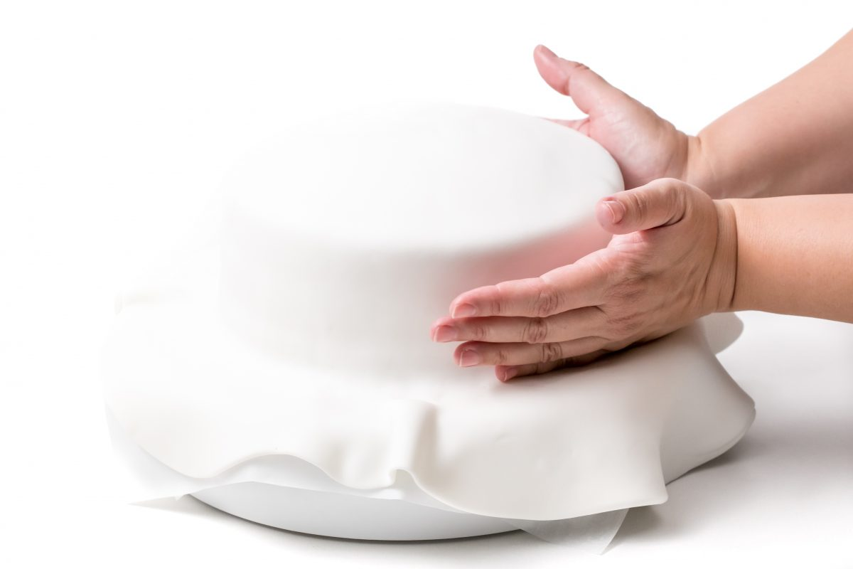 USE THE SIDE OF THE HANDS TO PRESS THE EDGES OF THE FONDANT AT THE BASE OF THE CAKE