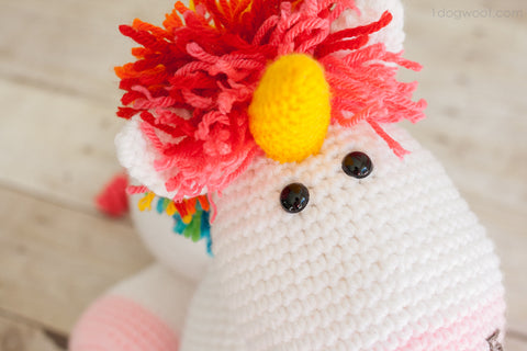 zoom on the head of the unicorn with its yellow horn