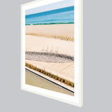 Angled view of a large white wood frame with a fine art print featuring Baja beaches.