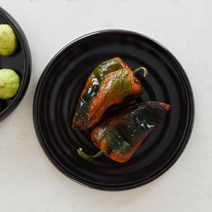 A black stoneware dinner plate with two poblano peppers.