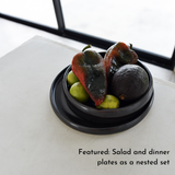 A nested set of black stoneware plates with peppers and fruit.