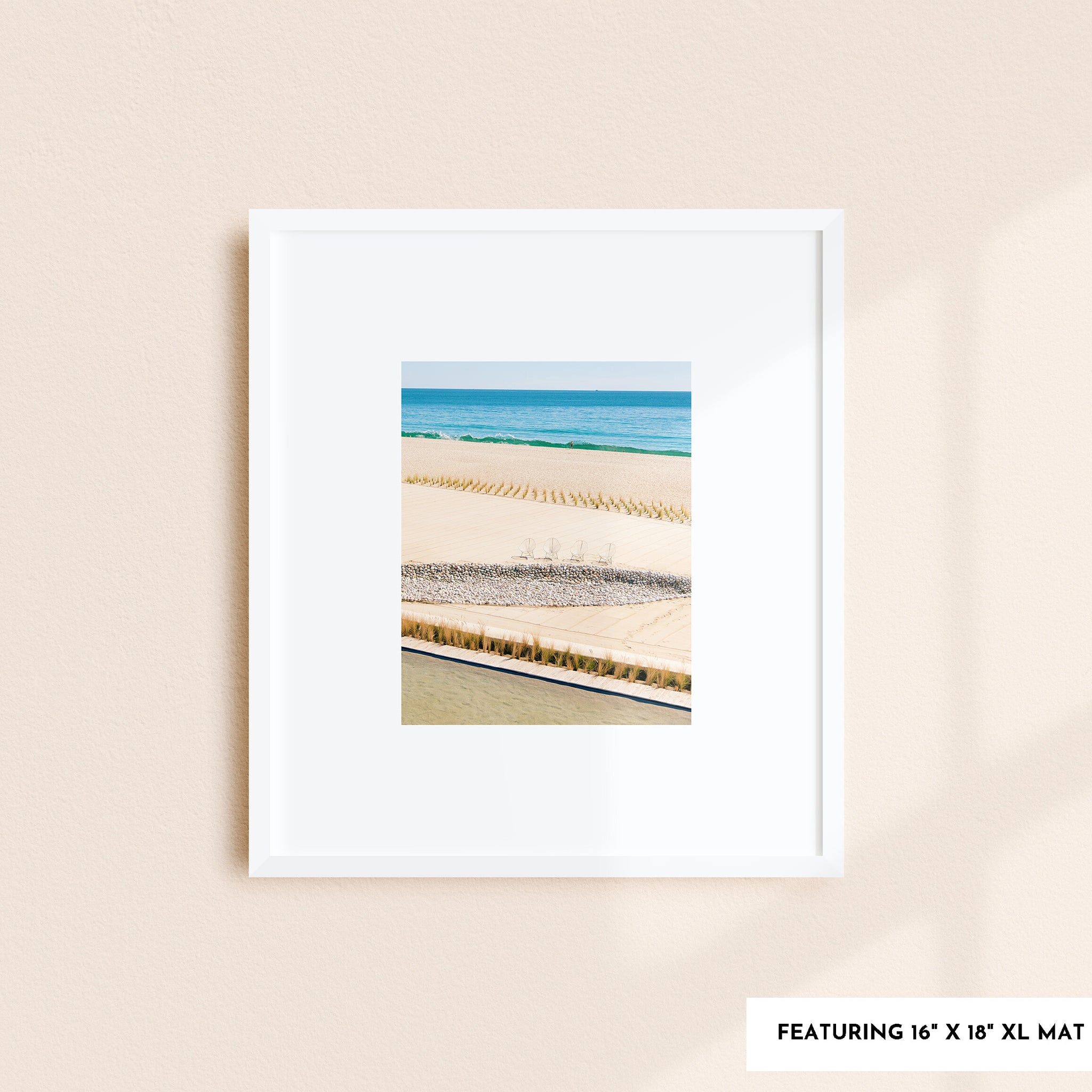 "A framed art print with an extra-large 4"" white mat against a peach colored wall."
