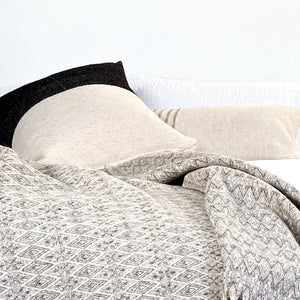 A collection of ivory, black and gray colored wool throw pillows and blankets on a bed.