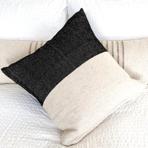 A black and ivory wool throw pillow, handwoven in Guanajuato, Mexico, on a bed with a handwoven wool lumbar pillow and cozy white bedding.