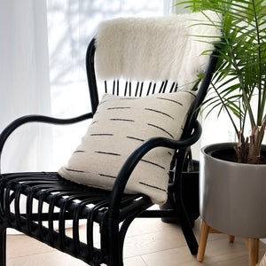 An ivory wool throw pillow with black stripes on black wicker chair next to a bright window and a tall palm plant.