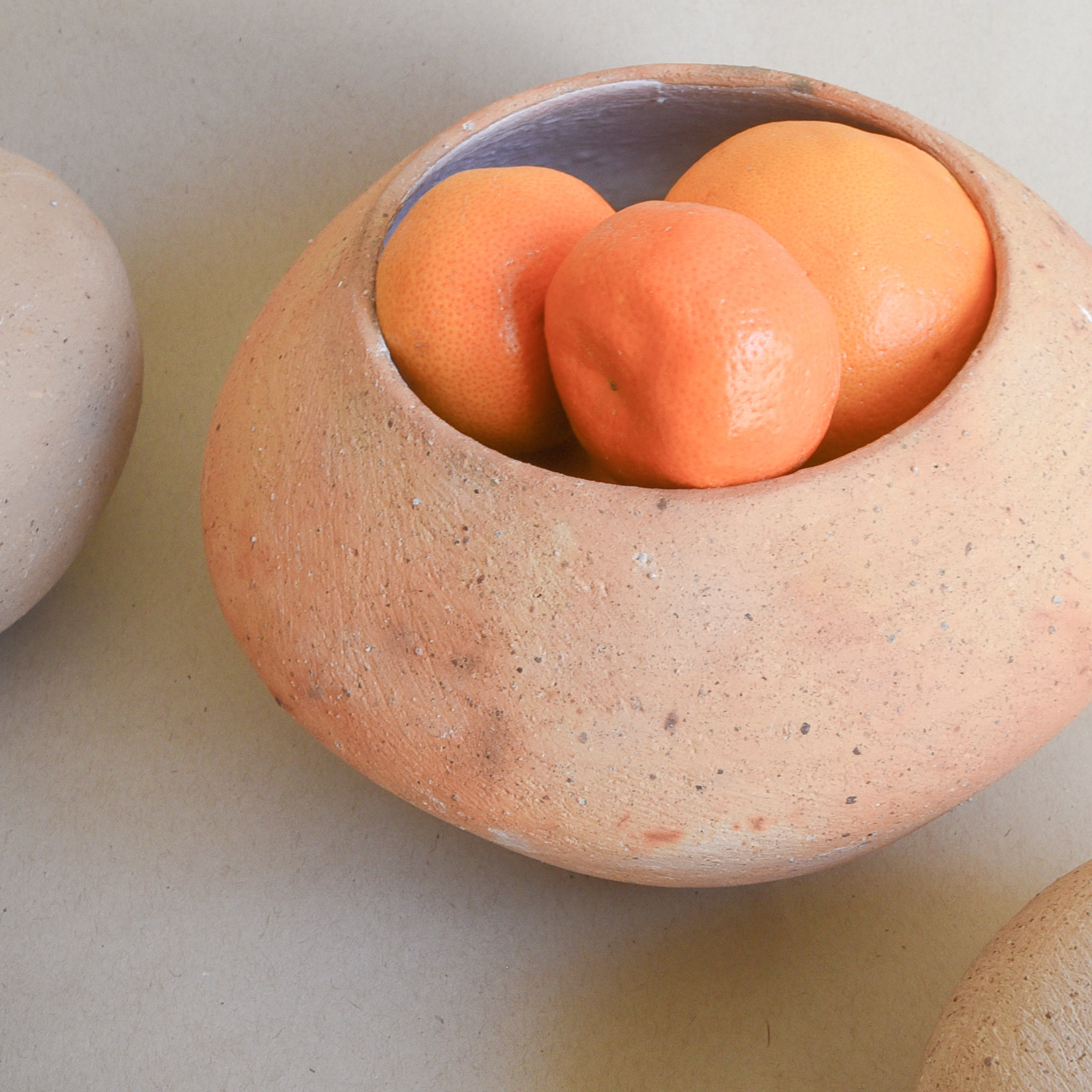 A large terracotta ceramic vase filled with oranges.