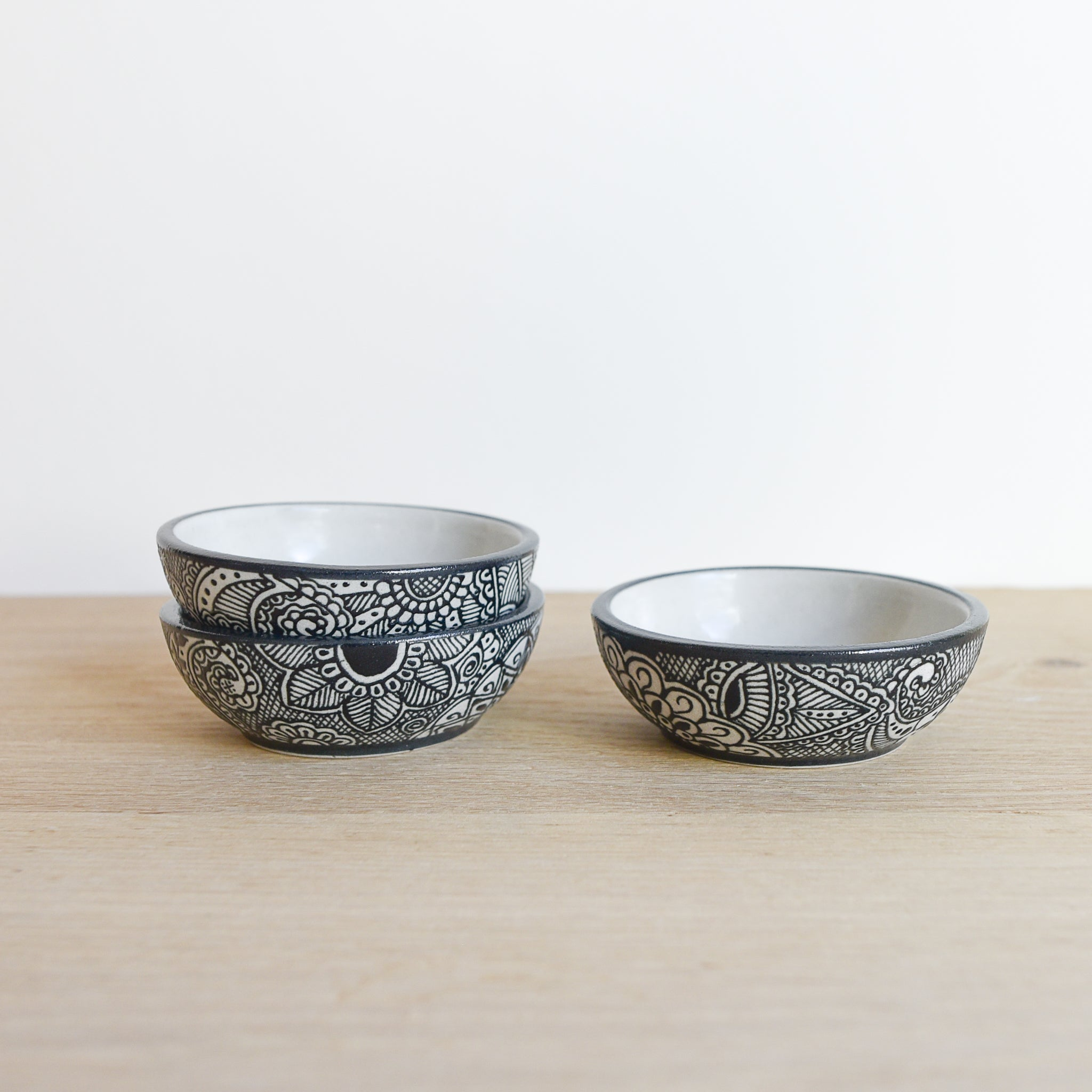 Small hand-painted black and ivory clay talavera style bowls made in Mexico.