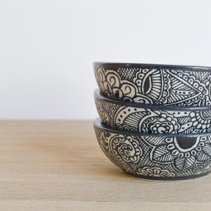 A set of stacked clay talavera style bowls on a light wood table.