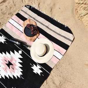 A Mexican serape blanket on a beach.