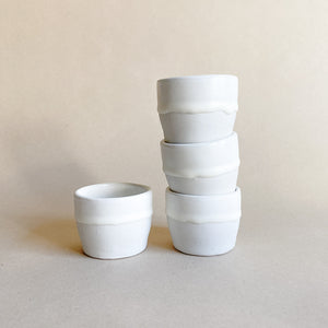 A set of four white glazed mezcal cups made of porcelain clay.