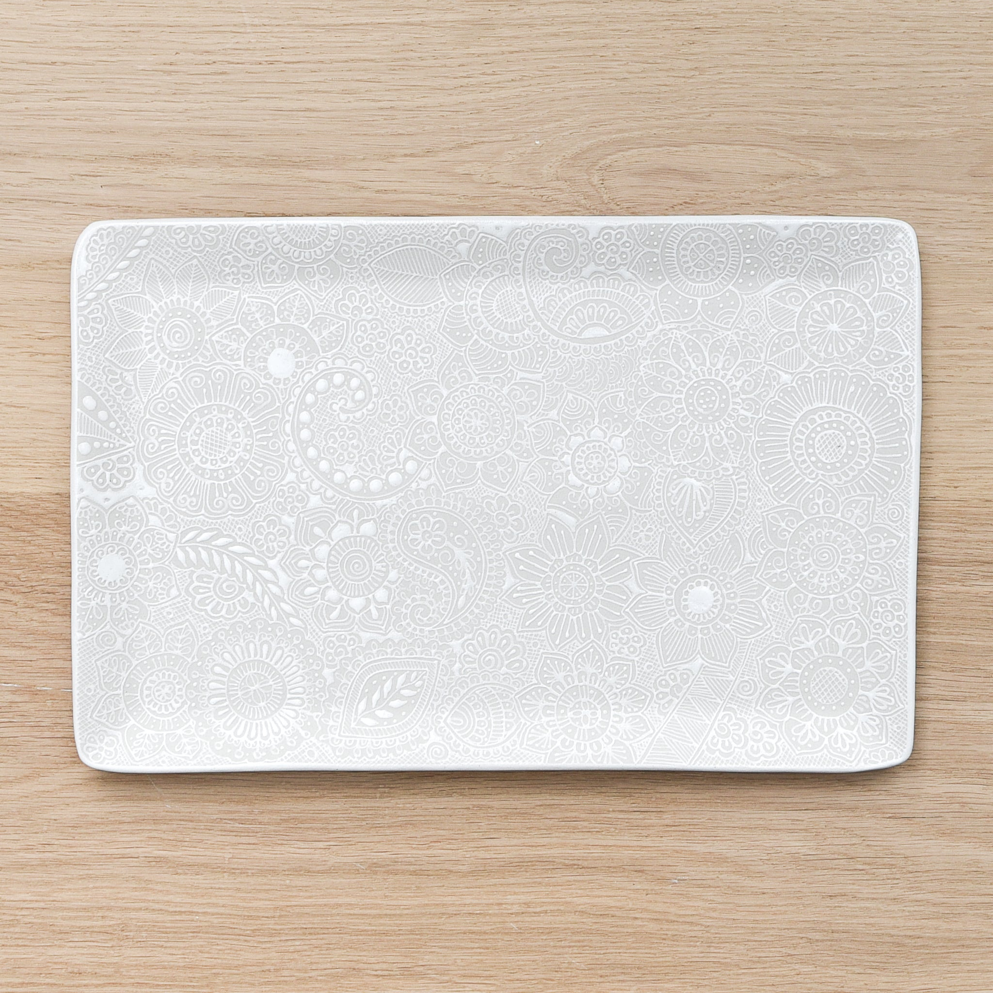 A large white ceramic serving tray made in Mexico on a light wood table.