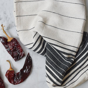 Black and ivory kitchen hand towel on a white marble counter with dried red peppers.