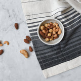 An ivory, black and grey hand towel on a white marble counter with a bowl of mixed nuts.