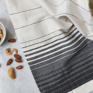 A handwoven Oaxacan hand towel on a white marble counter next to a bowl of nuts.