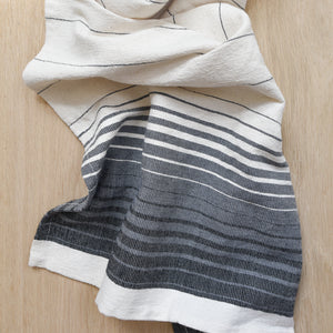 An ivory, black and grey hand towel on a light wood table.