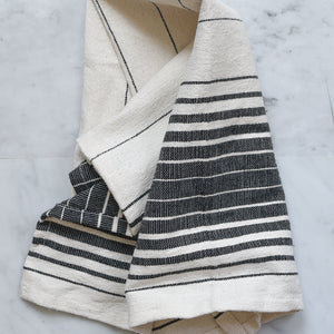 An ivory and black striped hand towel handwoven in Oaxaca, Mexico on a marble counter.