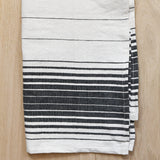 A black and ivory kitchen towel on a light wood table.