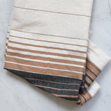 A ivory, rust and black colored hand towel on a white marble counter.