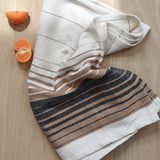 A striped hand towel made in Oaxaca, Mexico on a light wood table with a sliced tangerine.