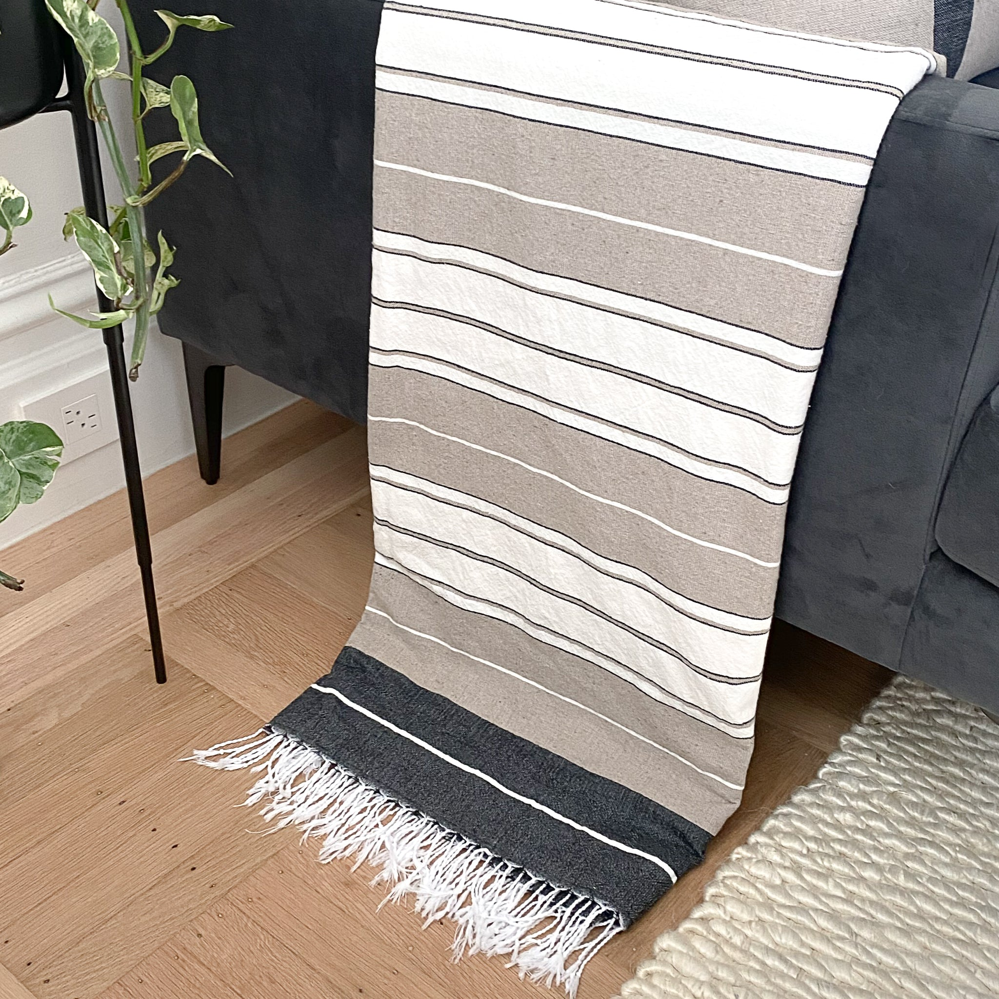 A sandy beige, white and dark grey striped cotton throw hanging over the arm of a dark grey velvet couch.