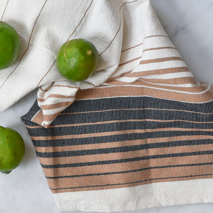 An ivory handwoven kitchen towel on a white marble counter with limes.