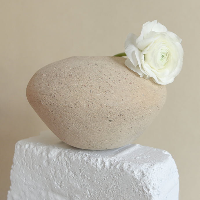 A small ceramic vase with a stone-like texture containing white flowers is on a white brick with a beige background.