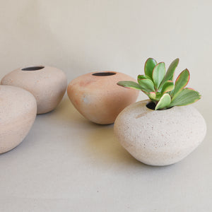 A set of small stone-like ceramic vases made in Guadalajara, Mexico and styled with a small succulent.