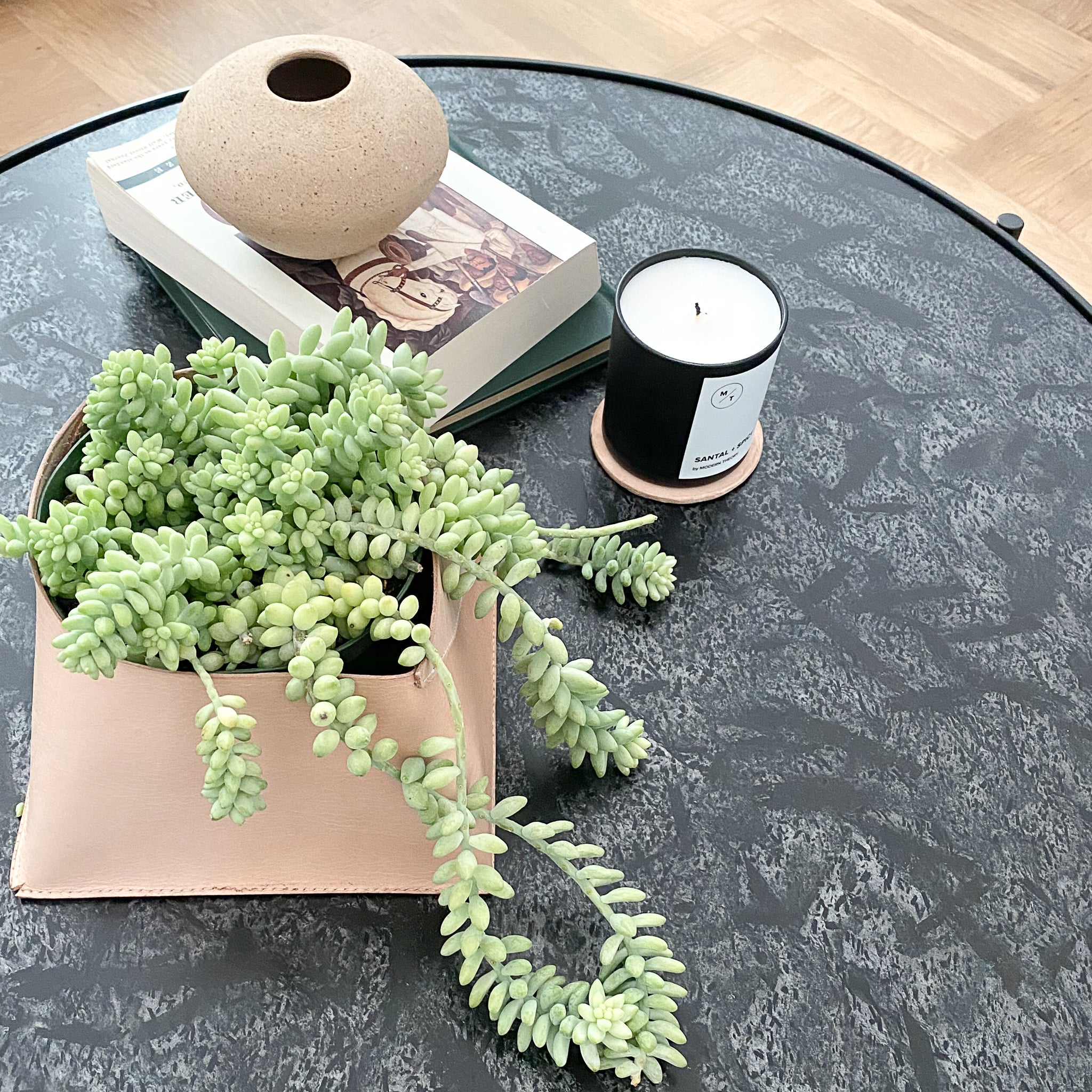 A black marble coffee table styled with a natural leather bin holding a sprawling succulent. Also featured is a black candle, leather coaster and set of books.