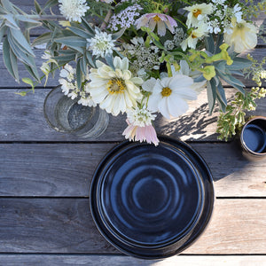 Black stoneware salad and dinner plates on a wood table with a bouquet of white flowers.