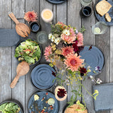 A wood table scattered with black stoneware dinner and salad plates, a bouquet of flowers, serving utensils and food.