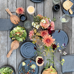 A wood table scattered with black stoneware dinner and salad plates, various serving utensils, candles, and a bouquet of flowers.