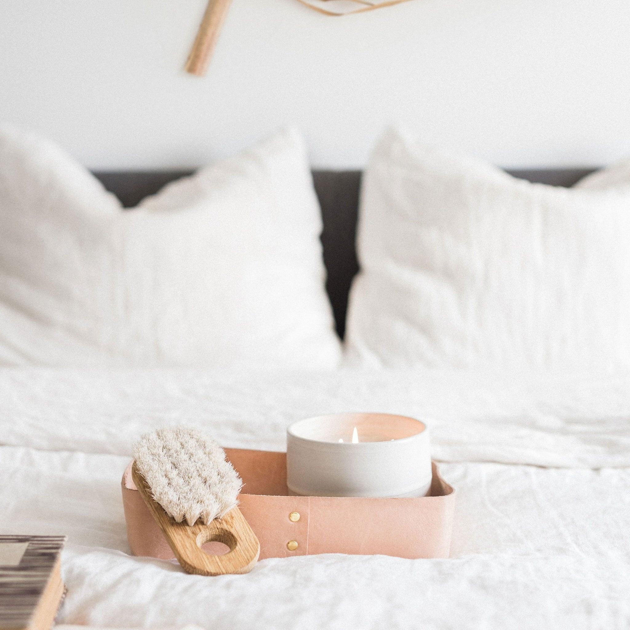 A leather tray holding a large white candle a wooden brush on a bed with white bedding.
