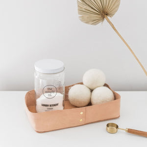 A leather tray holding powder laundry detergent and wool dryer balls sits on a white wood table with a dried palm in the background.