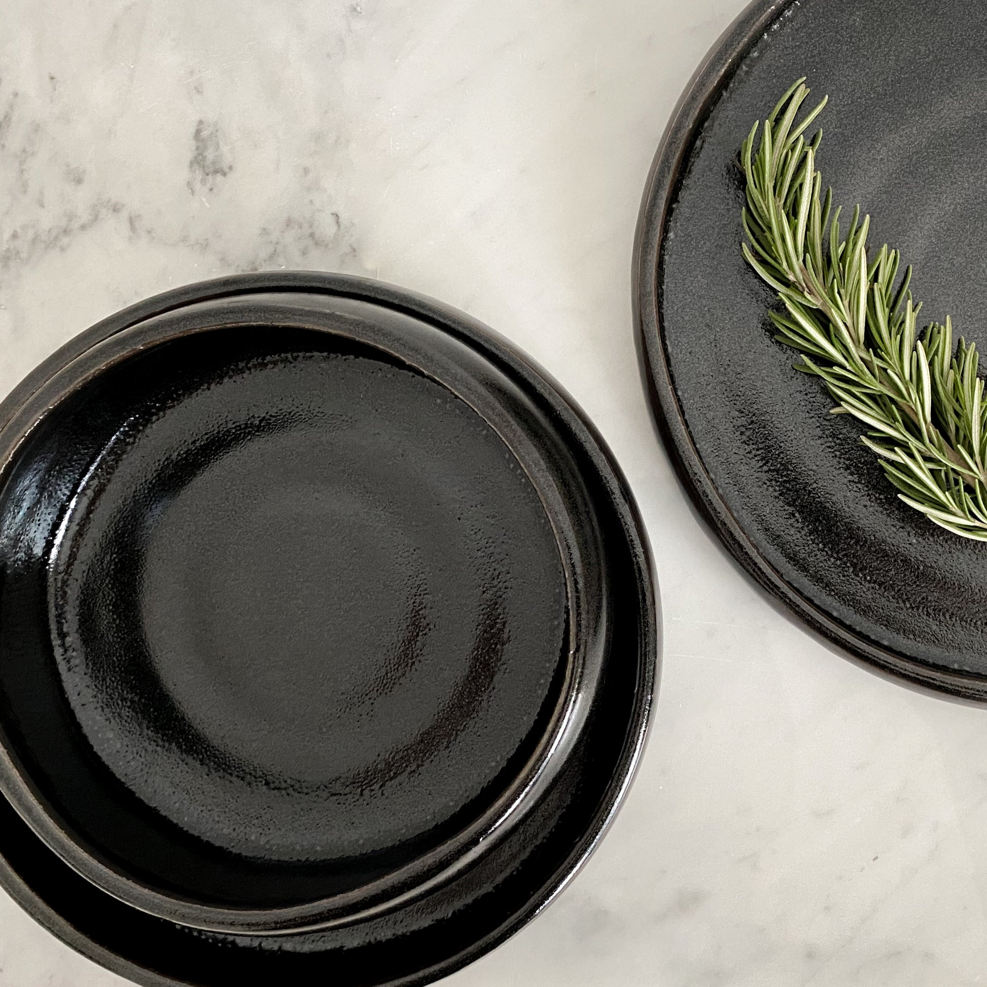 A marble counter with a black stoneware dinner set including a salad plate, dinner plate and nested bowl.