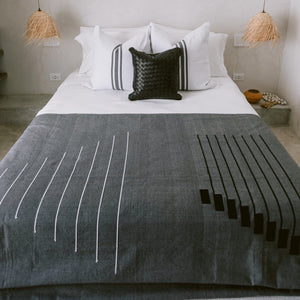 A dark gray cotton coverlet with handstitched details draped over the top of a bed.